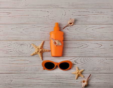 Glasses of orange color and sunscreen on a wooden background. Selective focus. Stock Photo