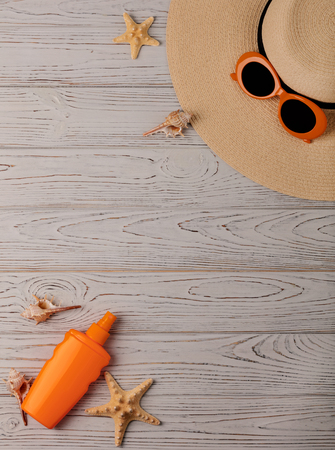 Fashion accessories - hat, orange glasses and sunscreen on a wooden background. Selective focus. Banque d'images