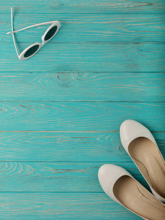 Womens shoes and white sun glasses on a blue wooden background. Selective focus. Stock fotó