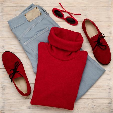 Ensemble de blue jeans, pull, chaussures et accessoires de couleur rouge sur un fond en bois. Mise au point sélective Banque d'images
