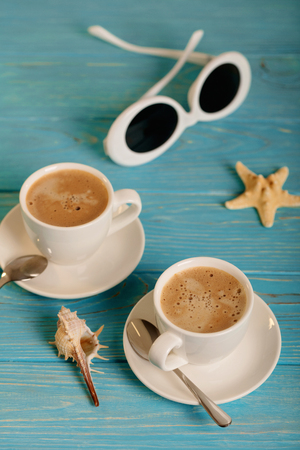 Sunglasses and two white cups of coffee on a wooden blue background. Selective focus. Stock Photo