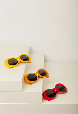 Sunglasses of red, orange and yellow colors on a white background. Selective focus.