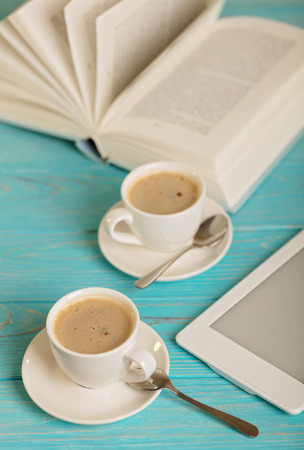 Book, e-book and two white cups of coffee on a wooden blue background. Selective focus.