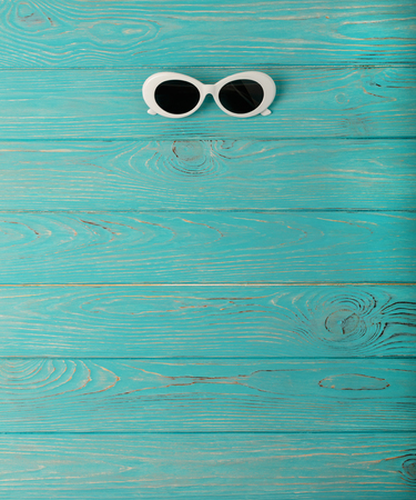 Womens white sun glasses on a blue wooden background. Selective focus.