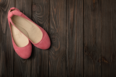 Pink women's shoes (ballerinas) on wooden background. Selective focus.