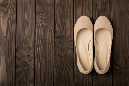 Beige women's shoes (ballerinas) on wooden background. Selective focus.