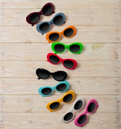 Collection of fashionable multi-colored sunglasses - a trend of summer on wooden background. Selective focus. Stock Photo