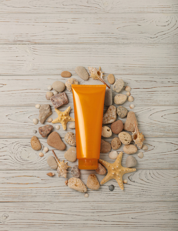 Suntan cream on a gray wooden background, shells, sea stones and a starfish. Selective focus.