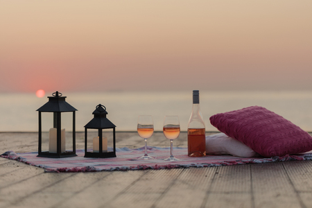Summer sea sunset. Romantic picnic on the beach. Bottle of wine, glasses, candles, plaid and pillows. Selective focus. Zdjęcie Seryjne - 108459905
