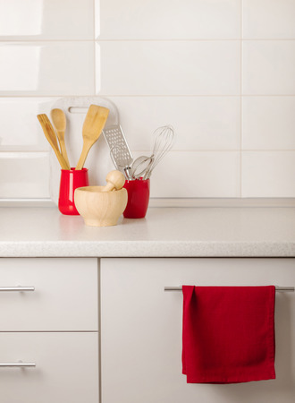 Interior white kitchen with kitchen tools and red crockery. Selective focus. 写真素材