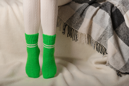 Female legs in warm white knitted tights and green socks on a white background made of faux fur.