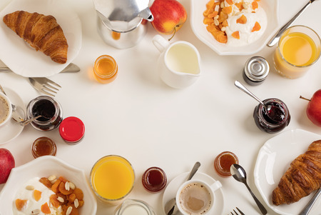Breakfast time. Croissants and orange juice, jam and honey. Coffee with cream or milk. Fruits - bananas, red and green apples. Ricotta with sour cream, nuts and dried apricots. Breakfast on a white table. View from above.