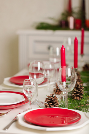 Merry Christmas and Happy New Year! D¢able setting festive decor - white and red dishes, red candles in the candlesticks, juniper branches and fir cones. Selective focus.