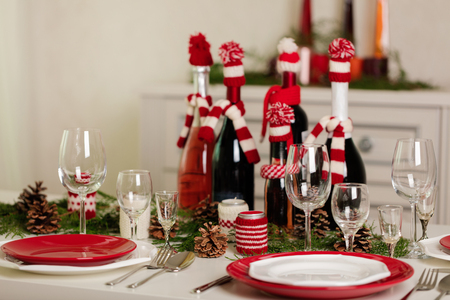 Merry Christmas and Happy New Year! D¢able setting holiday knitted decor - Santa Claus knitted hats on the bottle with wine, candles in candlesticks in knitted decor. Selective focus.