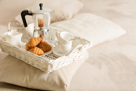 Breakfast in bed. On a white wicker tray there is a coffee maker, coffee white cups and croissants. Selective focus.