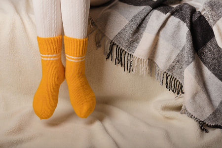 Female legs in warm white knitted tights and yellow socks on a white background made of faux fur.