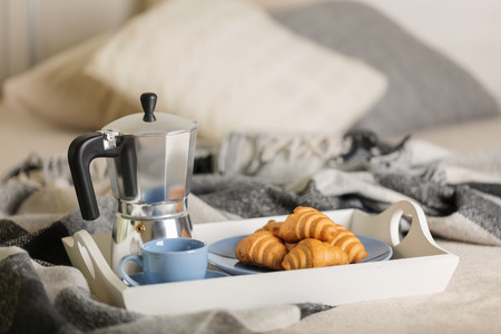 Breakfast in bed. On a white tray there is a coffee maker, coffee blue cup and croissants. Selective focus.