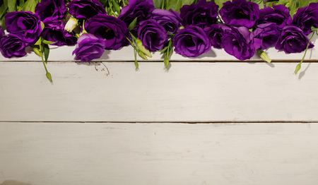Violet flowers - eustoma, on a white wooden background. Copy space.