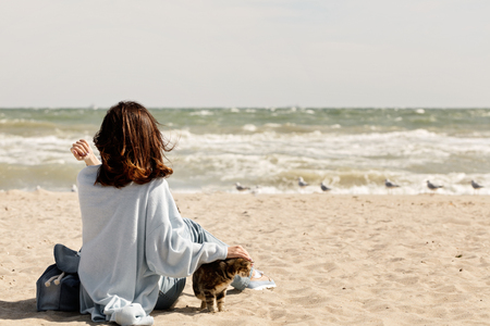 Young woman (brunette) in a light blue cardigan and jeans, with a backpack, sits on the beach and plays with a cat. Selective focus.