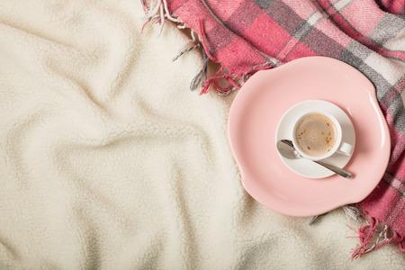 Horario de invierno. Una acogedora manta rosa cálida y una taza de café y croissants en la cama. Enfoque selectivo. Foto de archivo