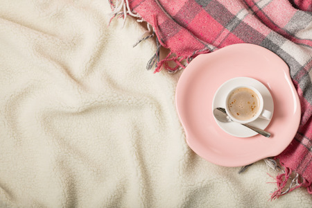 Winter time. A cozy warm pink blanket and a cup of coffee and croissants on the bed. Selective focus.