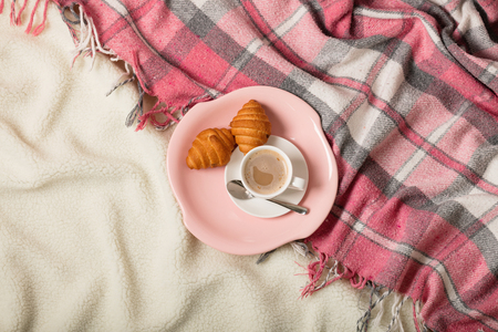 Winterzeit. Eine kuschelige warme rosa Decke und eine Tasse Kaffee und Croissants auf dem Bett. Selektiver Fokus.