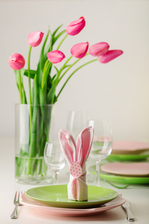 Happy easter. Decor and table setting of the Easter table is a vase with pink tulips and dishes of pink and green color. Selective focus.