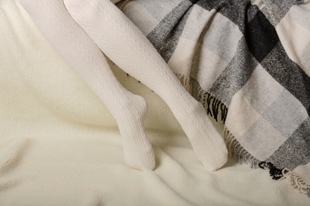Female legs in warm white knitted tights on a white background made of faux fur.