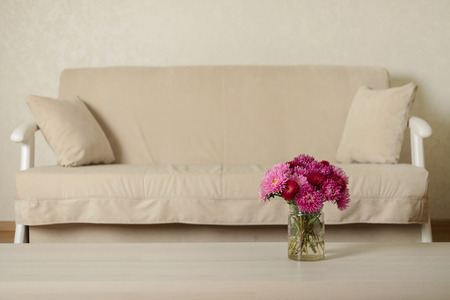 Beige sofa with pillows in the living room and vase with Flowers (Michaelmas daisy, asters). Selective focus.