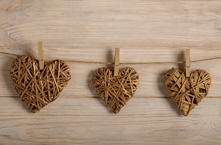 Happy Valentine's Day! Decorative wicker hearts of gold color on a light wooden background. Selective focus.
