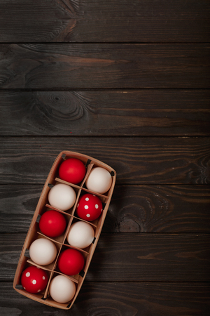 Happy Easter! Painted Easter eggs - red, white and red with white polka dots on a brown wooden background. Selective focus.