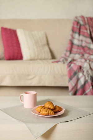 Beige sofa with plaid, colorful pillows (pink, grey, white) and coffee with croissantsin the living room. Selective focus.