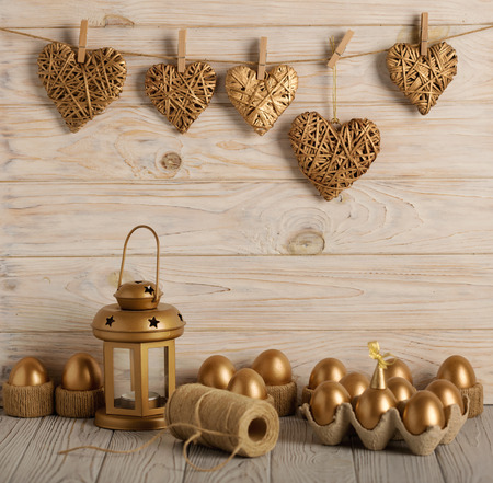 Happy easter! Easter decor and Easter eggs of golden color on a light wooden background. Selective focus.