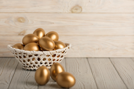 Happy easter! Easter eggs of golden color on a light wooden background. Selective focus.