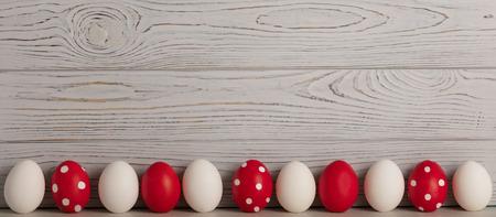 Frohe Ostern! Bemalte Ostereier - rot, weiß und rot mit weißen Tupfen auf grauem Holzhintergrund. Selektiver Fokus. Standard-Bild