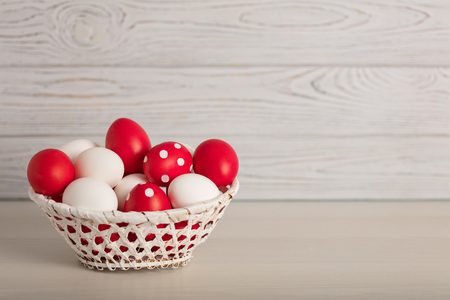 Happy Easter! Painted Easter eggs - red, white and red with white polka dots on a gray wooden background. Selective focus.