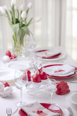 Happy easter. Decor and table setting of the Easter table is a vase with white tulips and dishes of red and white color. Easter colored eggs with white polka dots. Selective focus. 免版税图像