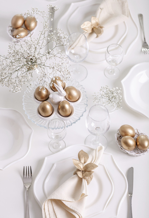 Happy Easter! Golden decor and table setting of the Easter table with white dishes of white color. Selective focus.