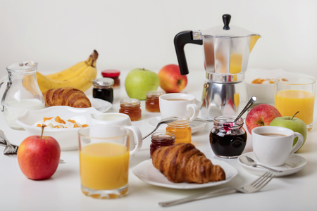 Breakfast time. Croissants and orange juice, jam and honey. Coffee with cream or milk. Fruits - bananas, red and green apples. Ricotta with sour cream, nuts and dried apricots. Breakfast on a white table.