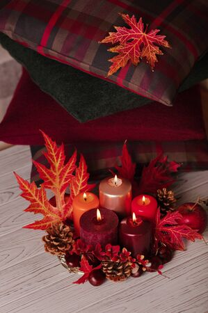 Autumn still life - candles, leaves and cones on the background of pillows. Selective focus.