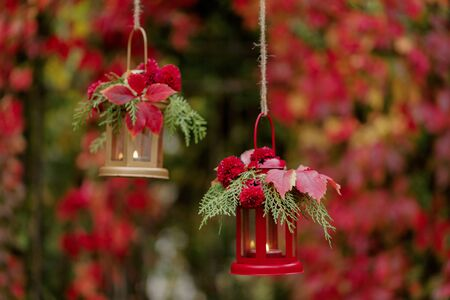 Fall time. Autumn decoration. Candlesticks in the form of lanterns with daisy decor, juniper and autumn red leaves. Selective focus.