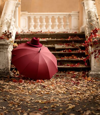 Autumn leaf fall. Red and yellow leaves on the destroyed old stone steps burgundy (marsala color) umbrella and hat. Blur effect.