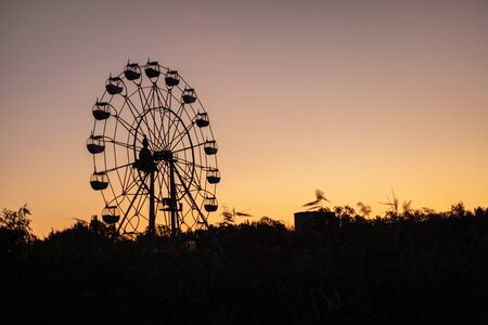 Silhouette of a ferris wheel at sunrise (sunset) of the sun on a background of trees and grass. Beautiful background with copy space. 免版税图像
