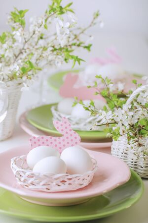 Happy easter. Decor and table setting of the Easter table is a vase with pink tulips and dishes of pink and green color. Selective focus. 免版税图像