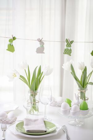 Decor and table setting of the Easter table is a vase with white tulips and dishes of green and white color. Easter decor with white polka dots. Selective focus. 免版税图像