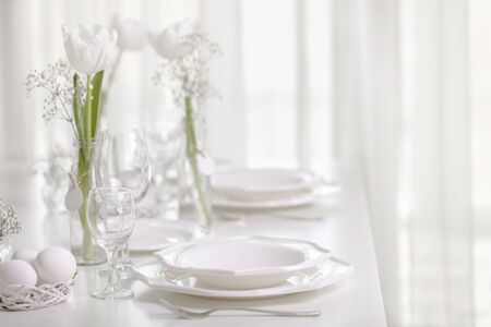 Happy Easter! Decor and table setting of the Easter table with white tulips and dishes of white color.  Selective focus.