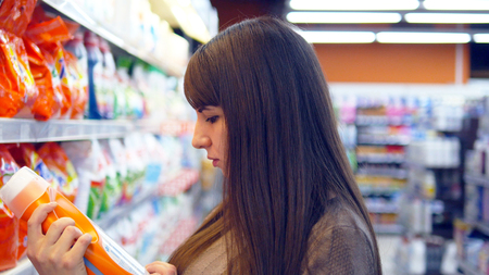 Young woman choosing household chemicals in supermarket. Beautiful girl selects fabric softener or washing powder at the store and put it a shopping cart. Department of cleaning product and home care Imagens