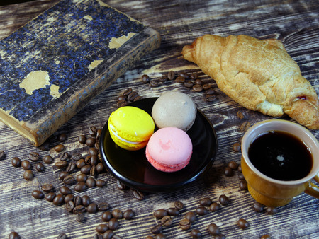 Black coffee and multicolored macarone on vintage background