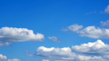white fluffy clouds over blue sky on sunny day