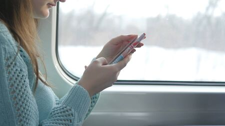 Young girl traveling in a train and using mobile phone. Beautiful woman sends a message from the smartphone. Attractive girl chatting with friends. Passing train at window. Close up